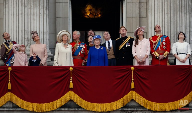 """Britain's Queen Elizabeth II, centre, surrounded by members of her family, watch a Royal Air Force fly pass by, on the balcony of Buckingham Palace, during the Trooping The Colour parade, in London, Saturday, June 15, 2013. Queen Elizabeth II celebrated her birthday with traditional pomp and circumstance - but without her husband by her side.  Prince Philip remains in the hospital, recovering from exploratory abdominal surgery. The queen invited her cousin, the Duke of Kent, to accompany her in a vintage carriage. Other royals — including Prince Harry and the Duchess of Cambridge — joined in the celebration Saturday. More than 1,000 soldiers, horses and musicians are taking part in the parade known as """"Trooping the Color,"""" an annual ceremony. From left, Prince Edward, the Earl of Wessex, Lady Louise, James, Viscount Severn, Sophie, the Countess of Wessex, Camilla, The Duchess of Cornwall, Prince Charles, Anne, the Princess Royal, Timothy Laurence,  Prince Andrew, Duke of York, Prince Harry, Kate, The Duchess of Cambridge, Prince William, Duke of Cambridge and Princess Eugenie.  (AP Photo/Sang Tan)"""
