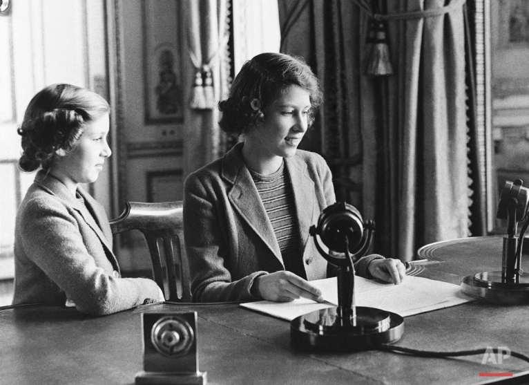 Performing one of the many public duties she will be called on, as a member of the Royal House, to fulfill as she grows older, Princess Elizabeth, center, 11-year-old heiress apparent to the British throne, is shown as she made her rapid debut, broadcasting a three-minute speech to British girls and boys evacuated overseas, Oct. 22, 1940, London. She is joined in bidding good-night to her listeners by her sister, Princess Margaret Rose.