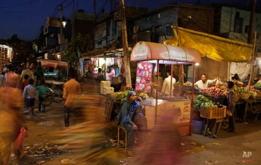 A roadside ice-cream vendor waits for customers at a market in New Delhi, India, Thursday, April 7, 2016. The Indian economy is characterized by the existence of a vast majority of informal or unorganized labor employment. (AP Photo/Altaf Qadri)
