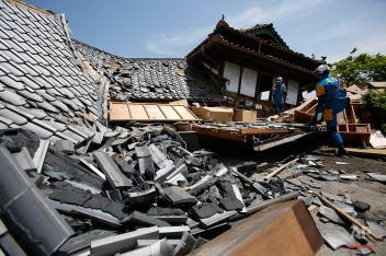Police rescue team members search through damaged houses to check possibility of trapped people in Mashiki, Kumamoto prefecture, southern Japan, Friday, April 15, 2016. Aftershocks rattled communities in southern Japan as businesses and residents got a fuller look Friday at the widespread damage from an unusually strong overnight earthquake. (AP Photo/Koji Ueda)