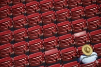 A spectator sits in the stands before an opening day baseball game between the Cincinnati Reds and the Philadelphia Phillies, Monday, April 4, 2016, in Cincinnati. (AP Photo/Michael Keating)