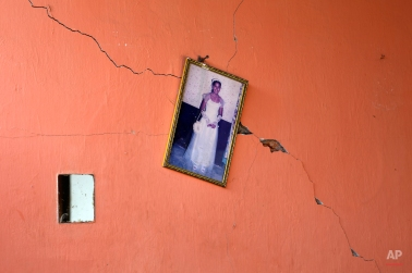 The portrait of a teenager hangs on a damaged wall after a 7.8-magnitude earthquake, in Canoas, Ecuador, Thursday, April 21, 2016. President Rafael Correa said Ecuador's worst earthquake in decades caused billions of dollars of damage and he is raising sales taxes and putting a one-time levy on millionaires to help pay for reconstruction. (AP Photo/Rodrigo Abd)