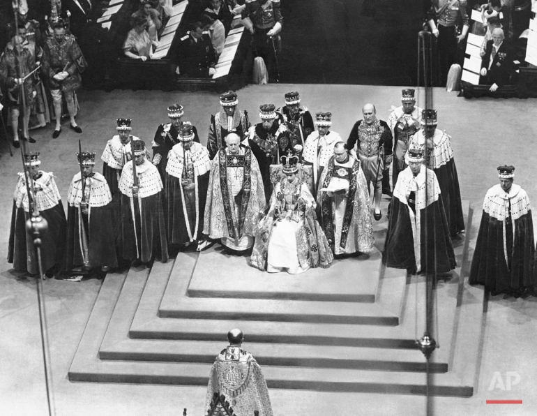 Surrounded by peers and churchmen, Queen Elizabeth II sits on throne in Westminister Abbey, London, June 2, 1953 after her coronation. The young monarch wears St. Edward's Crown and holds the Scepter with cross in her right hand and Rod with Dove in her left hand. Flanking the Queen are the Bishop of Durham, left, and the Bishop of Bath and Wells. In center foreground facing the Queen is the archbishop of Canterbury. (AP Photo)