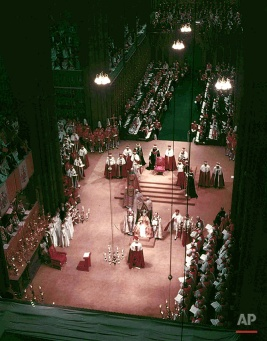 In this June 2, 1953 photo, Britain's Queen Elizabeth II, center bottom, sits in St. Edward's Chair, in Westminster Abbey, London, shortly before she was lifted onto the Throne during her Coronation. Britain's Queen Elizabeth celebrates her 90th birthday on Thursday, April 21, 2016. (AP Photo)