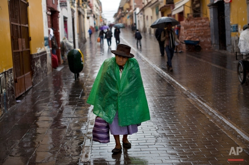 A woman walks in the rain, a day after general elections were held, in Ayacucho, Peru, Monday, April 11, 2016. Keiko Fujimori, the daughter of jailed former President Alberto Fujimori held a strong lead in preliminary results from the first round of Peru's presidential election and appeared headed to a showdown with another center-right candidate in a June runoff. (AP Photo/Rodrigo Abd)