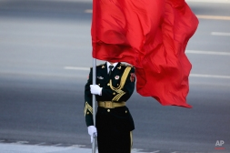 A member of a Chinese honor guard is covered by a red flag as he waits for the arrival of Sri Lanka's Prime Minister Ranil Wickremesinghe during a welcome ceremony outside the Great Hall of the People in Beijing, Thursday, April 7, 2016. (AP Photo/Andy Wong)