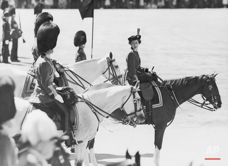 Queen Elizabeth II, of Great Britain, riding side-saddle on Imp, turns to Prince Philip (nearest camera) during the ceremony of trooping the color on Horse Guards Parade in London on June 13, 1957. The Duke of Gloucester, on the Queen's left, is partly hidden. (AP Photo/Eddie Worth)