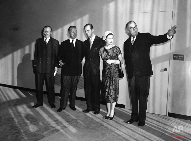 General Assembly President Sir Leslie Munro points to large windows and view from the Security Council chamber as Britain's royal couple tours United Nations headquarters in New York on Oct. 21, 1957.   Left to Right, are: Britain's Selwyn Lloyd, U.N. Secretary General Dag Hammarskjold, Prince Philip, Queen Elizabeth II and Sir Leslie.   Sun coming through windows casts shadows on the group. (AP Photo)