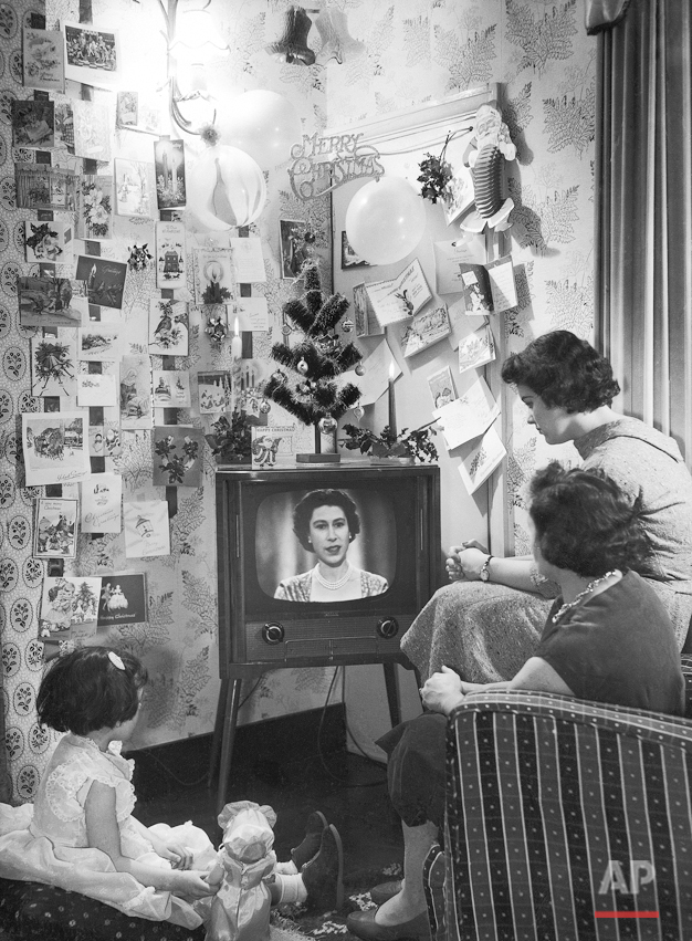 Mrs. Sidney Smart and her daughters, Sandra, 4, and Barbara, 15, look-in as Queen Elizabeth II  makes her Christmas broadcast on television on Christmas Day, Dec. 25, 1957. Her Majesty spoke from the long library at Sandringham, and was seen by both B.B.C. and I.T.V. viewers. It was the first time that the occasion has been televised. The Smart family live at Walthamstow, London. (AP Photo/Sidney Smart)