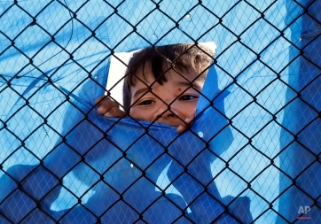 A migrant child looks out behind a wire fence of a refugee camp in the western Athens' suburb of Schisto, Monday, April 4, 2016, during the first day of the implementation of the deal between EU and Turkey. Under the deal, migrants arriving illegally in Greece will be returned to Turkey if they do not apply for asylum or if they make an asylum claim that is rejected. (AP Photo/Lefteris Pitarakis)