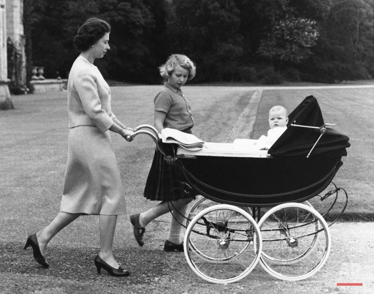 Queen Elizabeth II, of Great Britain, strolls in the grounds of her Scottish home in Balmoral castle, Scotland, Sept. 13, 1960, with Princess Anne and Prince Andrew in the perambulator. (AP Photo)
