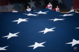 Volunteers hold a corner of a giant American flag before an opening day baseball game between the Cincinnati Reds and the Philadelphia Phillies, Monday, April 4, 2016, in Cincinnati. (AP Photo/John Minchillo)