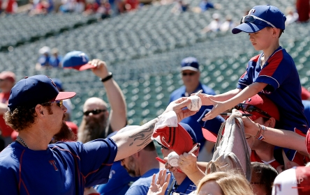 Texas Rangers Josh Hamilton, left, autographs a baseball for a young fan before a opening day baseball game against the Seattle Mariners, Monday, April 4, 2016, in Arlington, Texas. (AP Photo/Brandon Wade)