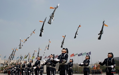 Members of a South Korean military honor guard throw their guns into the air during a weekly demonstration at the War Memorial of Korea in Seoul, South Korea, Friday, April 8, 2016. The honor guard's demonstration resumed Friday as it was suspended in winter and their performances in the honor guard ceremony attract foreign tourists and local visitors every year. (AP Photo/Lee Jin-man)