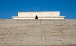 The top of the Lincoln Memorial appears behind a man as he pauses in his workout to stretch on the top step leading up from Ohio Drive Southwest and the Potomac River on a clear, crisp day in Washington, Friday, April 8, 2016. (AP Photo/Carolyn Kaster)