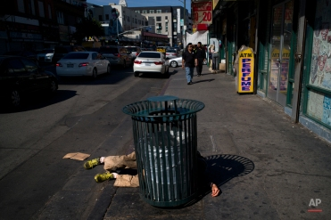 A homeless man sleeps on the sidewalk on Thursday, April 21, 2016, in downtown Los Angeles. (AP Photo/Jae C. Hong)