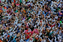 Devotees jostle to collect money showered on them by other devotees during a flag hoisting ceremony ahead of the annual festival marking the death anniversary of Sufi saint Moinuddin Chishti, in Ajmer, India, Monday, April 4, 2016. (AP Photo/ Deepak Sharma)
