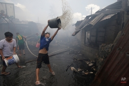 Filipino residents douse pails of water to help fight a fire which left at least 60 families homeless at a slum area in suburban Quezon city, north of Manila, Philippines, Friday, April 8, 2016. Firefighting forces go on the highest alert during the hot summer months when fire breaks out often nationwide. (AP Photo/Aaron Favila)