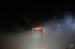 In this Wednesday, April 6, 2016 photo, Chinese People's Liberation Army Forces Hong Kong Building, center with red star, is partly covered by heavy fog in Hong Kong. Fog blanketing Hong Kong is common in springtime and may greatly affect shipping and aviation. (AP Photo/Vincent Yu)