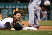 Pittsburgh Pirates' John Jaso slides into third with a triple as St. Louis Cardinals third baseman Matt Carpenter leaps over him to retrieve an overthrown ball during the fifth inning a baseball game in Pittsburgh, Wednesday, April 6, 2016. Jaso was allowed to score after the overthrown ball went into the stands. (AP Photo/Gene J. Puskar)
