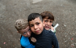 Children pose for a photo in a facility for refugees in Principovac, about 100 km west from Belgrade, Serbia, Friday, April 8, 2016. Migrants stuck on the Serbian side of the frontier since early March when Balkan countries abruptly shut their borders to migrants wanting to reach Germany and other seemingly wealthy Western European countries.(AP Photo/Darko Vojinovic)