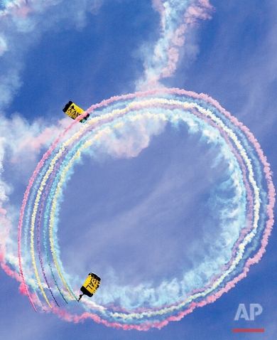 Members of the Navy Seal's parachute to the ground trailing colored smoke as the jump team performed during a rehearsal for this weekend's Smoky Mountain Air Show at the Tennessee Air National Guard base, Friday, April 15, 2016, in Knoxville, Tenn. (Tom Sherlin/The Daily Times via AP)