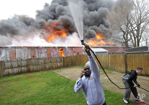 Greg Garmon, Sr. uses a garden hose to wet the side of his house in Erie, Pa., as a warehouse fire rages in the background on Monday, April 11, 2016. Multiple fire crews responded to the fire. (Christopher Millette/Erie Times-News via AP)