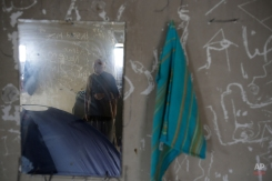 A migrant man is reflected in a mirror inside the room where he lives in a tent near the official Greek - Macedonian border station in Evzoni, Greece, Wednesday, April 6, 2016. Stranded migrants chosen to spend their days in an abandoned building near the official Greek - Macedonian border station in Evzoni, Northern Greece waiting for borders to be opened and living in conditions without running water or electricity under tent or in abandoned building. (AP Photo/Amel Emric)