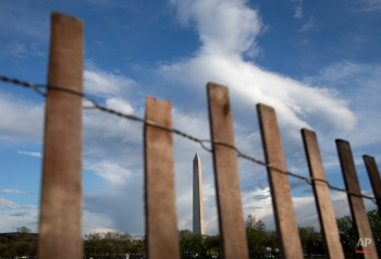 The Washington Monument is seen through a fence lining the Ellipse, in Washington, Thursday, April 7, 2016. (AP Photo/Carolyn Kaster)