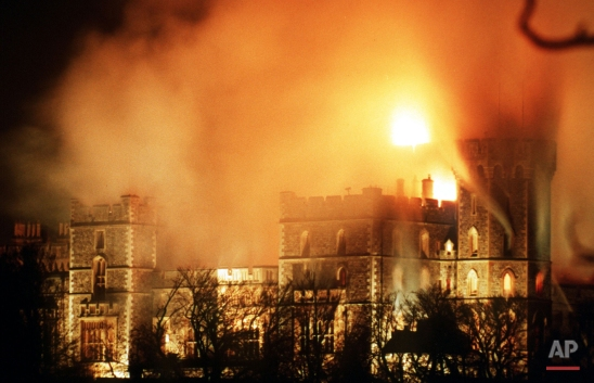 Hours after the major fire started flames continued to rise over Windsor Castle, causing millions of pounds of damage. Windsor Castle 20 miles west of London is used by Britain's Queen Elizabeth II as a weekend home and contains many historic works of art. (AP Photo/Denis Paquin)