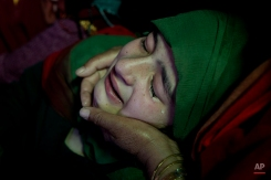 An unidentified relative of Raja Begum, a 70-year-old woman, who was hit by gunfire Tuesday, grieves during her funeral in Langate some 75 kilometers (47 miles) north of Srinagar, Indian controlled Kashmir, Wednesday, April 13, 2016. Indian authorities on Wednesday imposed a curfew in parts of Kashmir to stop fresh anti-India demonstrations following the killings of four people by Indian troops and a general strike called by separatists.(AP Photo/Dar Yasin)