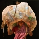 An Indian woman carries a sack of used plastic bottles to be sold at a recycled plant on the International Women's Day in the eastern Indian city of Bhubaneswar, India, Tuesday, March 8, 2016. (AP Photo/Biswaranjan Rout)