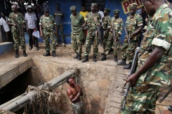 Jean Claude Niyonzima, a suspected member of the ruling party's Imbonerakure youth militia, pleads with soldiers to protect him from a mob of demonstrators after he came out of hiding in a sewer in the Cibitoke district of Bujumbura, Burundi, Thursday May 7, 2015. Niyonzima fled from his house into the sewer under a hail of stones thrown by a mob protesting President Pierre Nkurunziza's decision to seek a third term in office. (AP Photo/Jerome Delay)