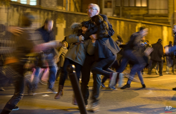 A man carries two children after panic broke out among mourners who payed their respect at the attack sites at restaurant Le Petit Cambodge (Little Cambodia) and the Carillon Hotel in Paris, Sunday, Nov. 15, 2015. Panic broke out as the crowd heard someone screaming from another location around the corner. Thousands of French troops deployed around Paris on Sunday and tourist sites stood shuttered in one of the most visited cities on Earth while investigators questioned the relatives of a suspected suicide bomber involved in the country's deadliest violence since World War II. (AP Photo/Peter Dejong)