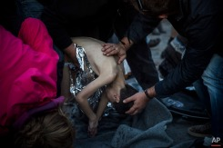 Paramedics and doctors try to revive a young boy after a boat with refugees and migrants sank while crossing the Aegean sea from Turkey to the Greek island of Lesbos, on Wednesday, Oct. 28, 2015. The condition of the child is not known. The Greek coast guard said it rescued 242 refugees or economic migrants off the eastern island of Lesbos Wednesday after the wooden boat they traveled in capsized, leaving at least three dead on a day when another 8 people drowned trying to reach Greece. (AP Photo/Santi Palacios)