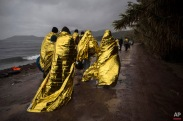 Refugees and migrants are covered with thermal blankets after their arrival on a dinghy from the Turkish coast to the Skala Sykaminias village on the northeastern Greek island of Lesbos, Friday, Oct. 23, 2015. The International Office for Migration says Greece over the last week experienced the largest single weekly influx of migrants and refugees this year, at an average of some 9,600 per day. (AP Photo/Santi Palacios)