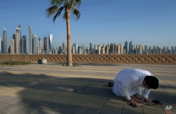 In this April 6, 2015 photo, with the Marina skyline as a backdrop, a Muslim man performs the afternoon prayer on Jumeirah Palm Island's walkway, in Dubai, United Arab Emirates. High-rise buildings, stacked row after row, make up this 50 million sq. foot (4.65 million sq .meter) waterfront neighborhood that is built around a man-made canal where the wealthy park their yachts. To mark its place in the world, the Dubai Marina boasts the world's tallest residential building. (AP Photo/Kamran Jebreili)