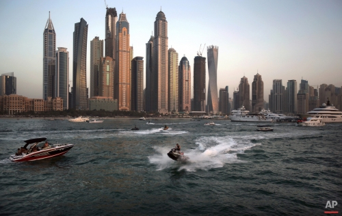In this Friday, April 10, 2015 photo, people use recreational vehicles opposite the Marina district of Dubai, United Arab Emirates. Dubai's year-round sunshine gives Marina a summer-vibe throughout the winter months, when temperatures rarely drop below a comfortable 75 degrees Fahrenheit (24 Celsius) during the day. On weekends, alcohol-fueled party boats ferry Russian and Western expatriates down the canal as speed boats and jet skis come out for a ride. (AP Photo/Kamran Jebreili)