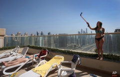 In this Sunday June 21, 2015 photo, a woman takes selfie at a swimming pool area on top of a residential building overlooking the Marina Waterfront and Sheikh Zayed highway in Dubai, United Arab Emirates.(AP Photo/Kamran Jebreili)