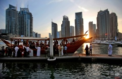 In this March 25, 2015 photo, tourists of different nationalities board a dhow for a cruise as the sun sets in the Marina neighborhood of Dubai, United Arab Emirates. Dubai's year-round sunshine gives the Marina a summer-vibe throughout the winter months, when temperatures rarely drop below a comfortable 75 degrees Fahrenheit (24 Celsius) during the day. (AP Photo/Kamran Jebreili)