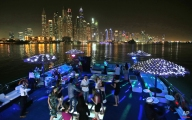 In this April 22, 2015 photo, guests dance on the GuGu boat during a private party opposite the skyline of the Marina Waterfront in Dubai, United Arab Emirates. Dubai's year-round sunshine gives Marina a summer-vibe throughout the winter months, when temperatures rarely drop below a comfortable 75 degrees Fahrenheit (24 Celsius) during the day. On weekends, alcohol-fueled party boats ferry Russian and Western expatriates down the canal as speed boats and jet skis come out for a ride. (AP Photo/Kamran Jebreili)