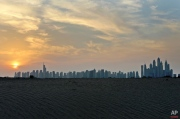 """In this Wednesday, Oct. 28, 2015 photo, the sun sets behind the skyscrapers of """"Marina Waterfront"""" and """"Jumeirah Lake Towers"""" districts as the skyline has seen from the sand dunes in Dubai, United Arab Emirates. In about 15 years after the inauguration of the Marina water canal more than 150 high rises were built on a piece of 3.5 square kilometres of empty land in Marina and more than 60 high rises in Jumeirah Lake towers. (AP Photo/Kamran Jebreili)"""
