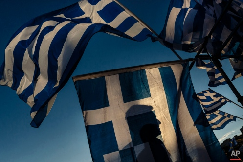 Series chronicling Greece's financial crisis. A pro-Euro demonstrator is silhouetted behind a Greek flag during a rally outside the Greek Parliament in Athens, Monday, June 22, 2015. Thousands of people gather to show support for the country's future in the eurozone and the European Union. (AP Photo/Daniel Ochoa de Olza)