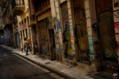 A man carry a box into the only shop open of an Athens street, Thursday, June 25, 2015. The ECB approved a request from Athens to increase the amount of emergency liquidity Greek lenders can tap from the country's central bank. Worried Greeks have been withdrawing their money from their country's banks, fearing the imposition of restrictions on banking transactions. An estimated more than 4 billion euros ($4.5 billion) left Greek banks last week. (AP Photo/Daniel Ochoa de Olza)