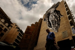 """A man walks down a street with a turned upside down mural inspired on """"The Praying Hands"""" by artist of the Renaissance Albrecht Durer, in Athens, Friday, June 26, 2015. The bitter standoff between Greece and its international creditors was extended into the weekend, just days before Athens has to meet a crucial debt deadline which could decide whether it goes bankrupt and gets kicked out of the euro currency club. (AP Photo/Daniel Ochoa de Olza)"""