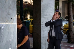 A woman withdraws money from ATM machine from the National Bank branch while another reacts behind her in central Athens on Saturday, June 27, 2015. Germany's vice chancellor says that a Greek referendum on the bailout talks could in principle make sense, but notes that it should be clear to voters what they will be deciding on. (AP Photo/Daniel Ochoa de Olza)