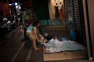A woman leaves a croissant next to an sleeping man living in the streets of central Athens, Thursday, June 25, 2015. The ECB approved a request from Athens to increase the amount of emergency liquidity Greek lenders can tap from the country's central bank. Worried Greeks have been withdrawing their money from their country's banks, fearing the imposition of restrictions on banking transactions. An estimated more than 4 billion euros ($4.5 billion) left Greek banks last week. (AP Photo/Daniel Ochoa de Olza)