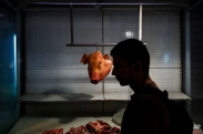 A pig's head hangs from a hook in a market in central Athens on Saturday, June 27, 2015. Germany's vice chancellor says that a Greek referendum on the bailout talks could in principle make sense, but notes that it should be clear to voters what they will be deciding on. (AP Photo/Daniel Ochoa de Olza)