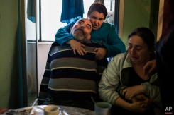 Juan Montiel, centre, suffers an epileptic seizures as his wife Marivi Leon del Valle, top, and his sister Maria Luisa Montiel, 47, right, help him during their eviction in Madrid, Spain on Tuesday, April 28, 2015. Maria Montiel, a former geriatric assistant, was living in a Bankia bank-owned apartment with her brother, Juan Montiel, 56, who has 46 percent disability, his wife, Marivi Leon del Valle, 54, who also has health problems and a friend, Jose Antonio Garcia Mendoza, 64. Out of work and dependent on small state benefits, they had been living on the street before renting a room in the apartment, which had been occupied by others that later left. The family tried to pay a token rent but the bank insisted on their eviction. Dozens of riot police carried out the eviction despite protests by housing rights activists. (AP Photo/Andres Kudacki)