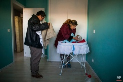 Furniture are packed behind the main door to stop riot police to enter the apartment as Cecilia Paredes and her husband Wilson Ruilova prepares to leave with their baby Dilan during their eviction in Madrid, Spain, Friday, Jan. 23, 2015. Paredes, 43, and her unemployed electrician husband Wilson Ruilova, 35, both from Ecuador, have three children: Dilan, a baby born less than two months ago; Andres, 16, and Miguel, seven. They have been unable to pay their rent after she lost her job as an elderly care assistant two years ago. The government company that owned the apartment sold it last year to an investor group along with more than 1,800 other apartments built for the needy and the new owner sought the family's eviction. (AP Photo/Andres Kudacki)